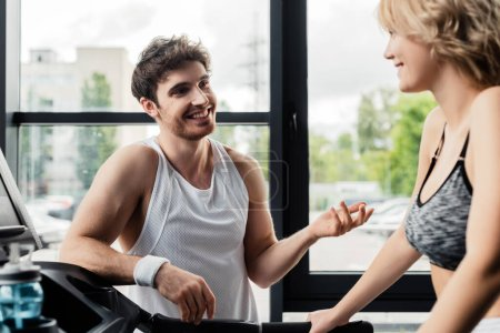 Photo for Selective focus of happy sportsman looking at girl in gym - Royalty Free Image