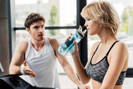 Selektiver Fokus attraktiver Sportlerin mit Sportflasche mit Wasser in der Nähe eines Mannes im Fitnessstudio