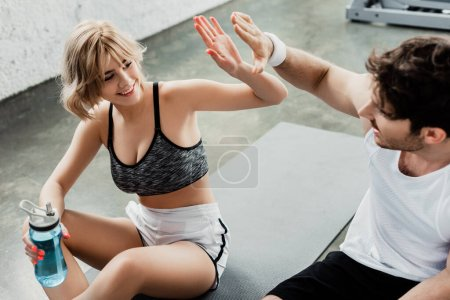 Photo for Selective focus of happy girl giving high five to man in gym - Royalty Free Image