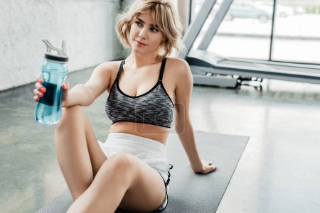 Photo for Attractive sportswoman holding sports bottle and sitting on fitness mat in gym - Royalty Free Image