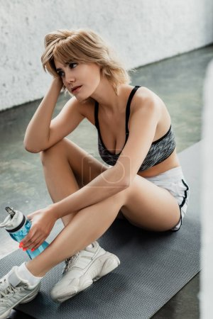 tired sportswoman holding sports bottle and sitting on fitness mat in gym