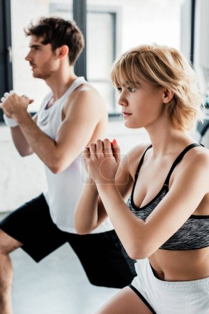Selektiver Fokus des Sportpaares mit geballten Händen beim Training im Fitnessstudio