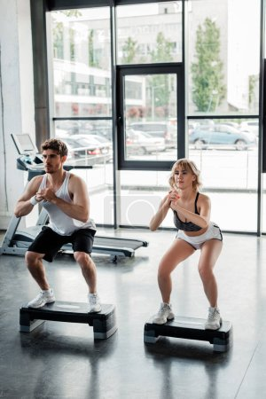 sportsman and sportswoman with clenched hands exercising near step platforms