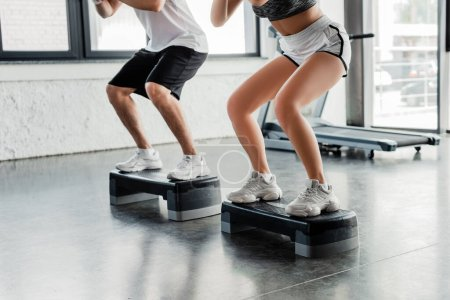 cropped view of sportsman and sportswoman exercising on step platforms