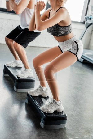 Photo for Cropped view of sportsman and sportswoman with clenched hands exercising on step platforms - Royalty Free Image