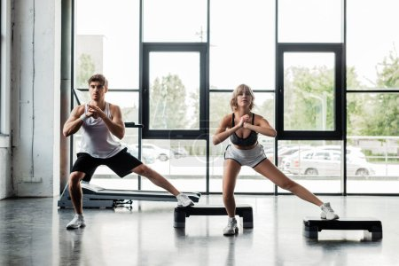 Photo for Young sport couple with clenched hands doing lunges exercising on step platforms - Royalty Free Image