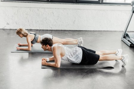 Photo pour Vue latérale du couple sportif faisant de la planche sur des tapis de fitness dans la salle de gym - image libre de droit