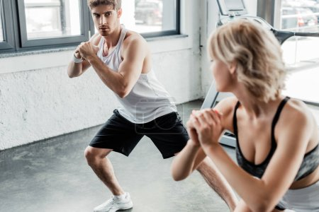 Photo for Selective focus of young sport couple with clenched hands looking at each other and exercising in gym - Royalty Free Image