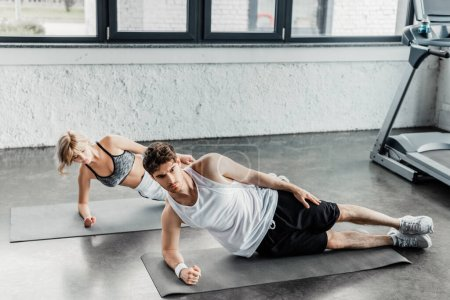 handsome sportsman and beautiful sportswoman exercising on fitness mats
