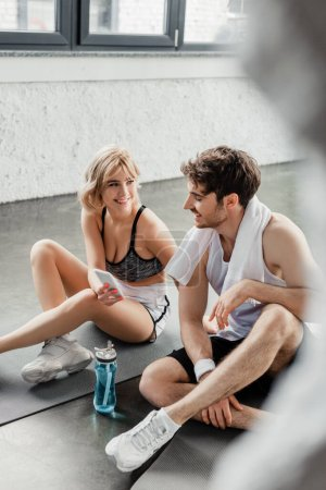 Photo for Selective focus of sportswoman holding smartphone and looking at handsome sportsman - Royalty Free Image