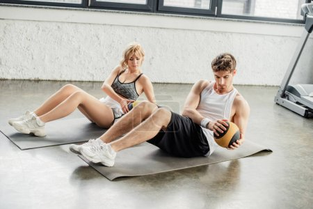 Photo for Handsome sportsman and sportswoman exercising with balls on fitness mats - Royalty Free Image