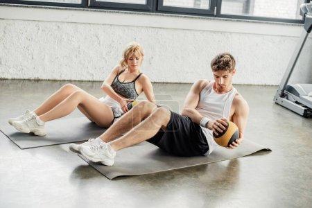 Photo pour Beau sportif et sportive faisant de l'exercice avec des balles sur des tapis de fitness - image libre de droit
