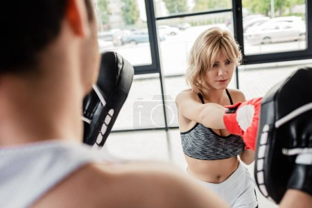 selective focus of sportive woman in boxing gloves punching man in boxing pads