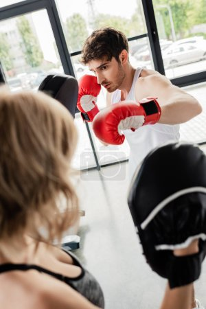 selective focus of sport couple in boxing gloves and boxing pads training in gym