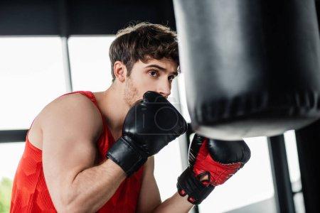 Photo pour Foyer sélectif du sportif dans les gants de boxe exercice avec sac de boxe - image libre de droit