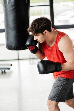 Photo pour Homme athlétique en vêtements de sport et gants de boxe travaillant avec un sac de boxe - image libre de droit