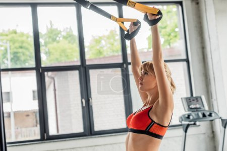 Photo for Athletic young woman in sportswear exercising with resistance bands in gym - Royalty Free Image