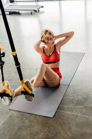 Photo for Selective focus of attractive woman in sportswear exercising with resistance bands while sitting on fitness mat - Royalty Free Image