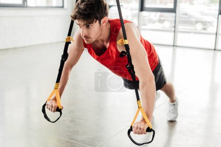 selective focus of handsome and athletic man working out with elastics in gym