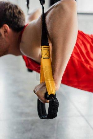 Photo pour Vue recadrée de l'homme fort travaillant avec des élastiques dans la salle de gym - image libre de droit