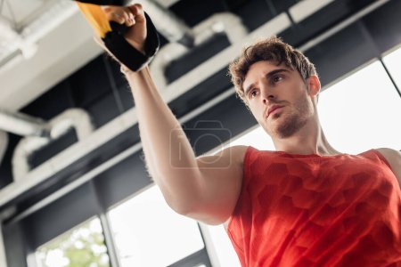 Photo for Low angle view of sportive man working out with elastics in gym - Royalty Free Image