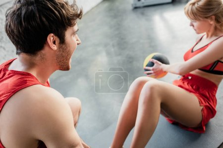 Photo for Selective focus of athletic man holding legs of sportswoman exercising with ball on fitness mat - Royalty Free Image