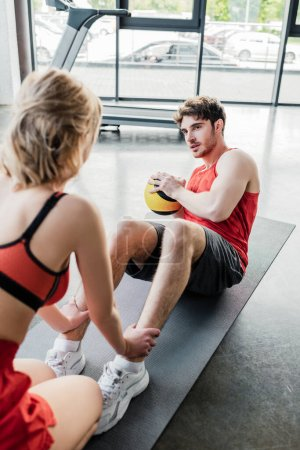 selective focus of sportive woman holding legs of sportsman exercising with ball on fitness mat