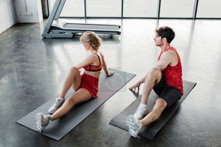 para sportowa w odzieży sportowej rozciągająca się na matach fitness w siłowni