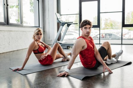 Photo for Young sport couple in sportswear stretching on fitness mats in gym - Royalty Free Image