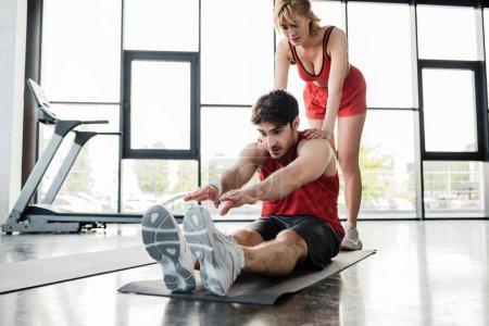 Photo pour Belle sportive touchant sportif sportif s'étirant sur tapis de fitness - image libre de droit