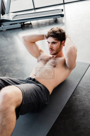Photo for Selective focus of muscular sportsman doing sit ups on fitness mat in gym - Royalty Free Image
