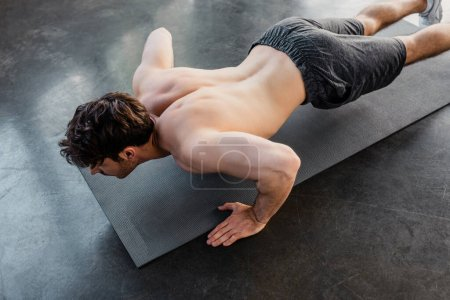 Photo for Overhead view of shirtless sportsman doing push ups on fitness mat in gym - Royalty Free Image
