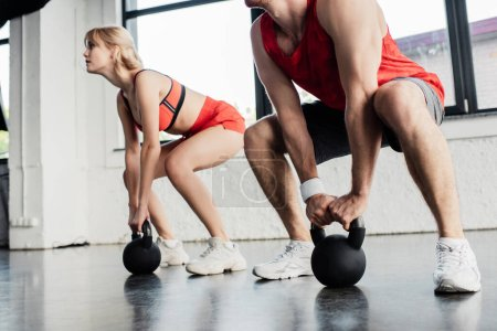selective focus of sport couple exercising with heavy dumbbells in gym