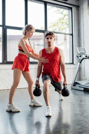 Photo pour Femme sportive touchant bel homme exerçant avec des haltères lourds dans la salle de gym - image libre de droit