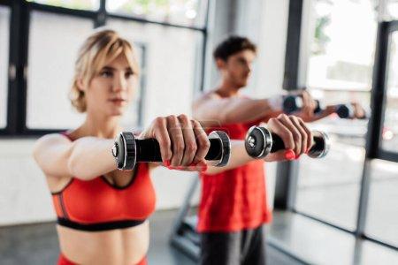 Photo pour Foyer sélectif du couple sportif travaillant avec des haltères dans la salle de gym - image libre de droit