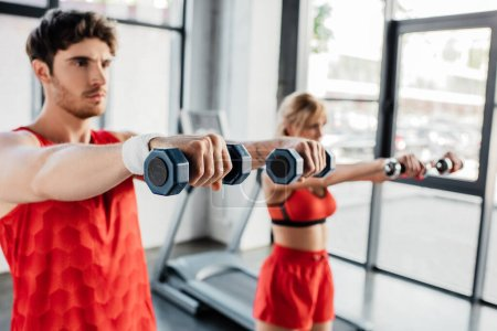 Photo for Selective focus of sportsman and sportswoman working out with dumbbells in gym - Royalty Free Image