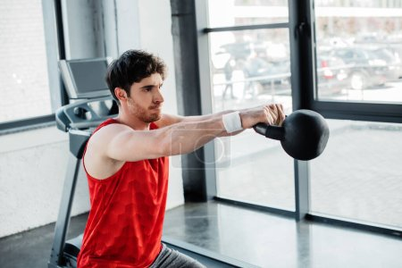 sportive man working out with heavy dumbbell in gym