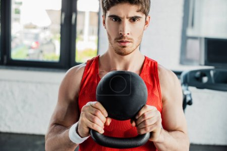 athletic man looking at camera and exercising with heavy dumbbell in sports center