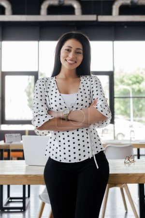 Photo for Happy businesswoman standing with crossed arms in office - Royalty Free Image