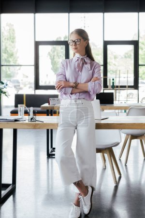 beautiful businesswoman in glasses standing with crossed arms in office