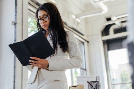 Photo pour Vue à angle bas d'une femme d'affaires attrayante dans des lunettes regardant un ordinateur portable au bureau - image libre de droit