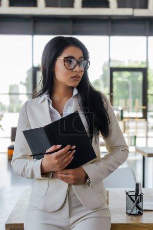 Photo pour Attrayant femme d'affaires tenant carnet et détournant les yeux - image libre de droit
