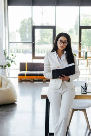 attractive businesswoman holding notebook and looking at camera in office