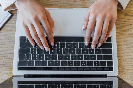 Photo pour Vue du haut de la femme tapant sur le clavier de l'ordinateur portable dans le bureau - image libre de droit
