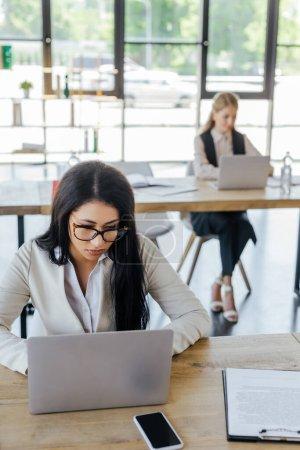 Selektiver Fokus der Geschäftsfrau in Brille, die in der Nähe ihres Bürokollegen arbeitet