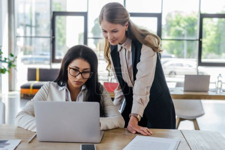 Photo for Beautiful businesswoman standing near attractive coworker in glasses and looking at laptop - Royalty Free Image