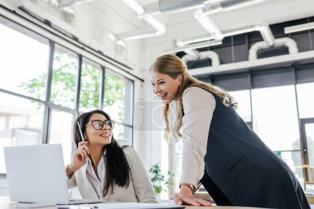 happy businesswoman in glasses looking at cheerful colleague in office