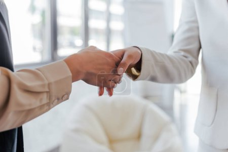 Photo for Cropped view of businesswomen shaking hand sin office - Royalty Free Image