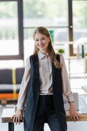 Photo pour Femme d'affaires heureuse debout près de la table dans le bureau moderne - image libre de droit