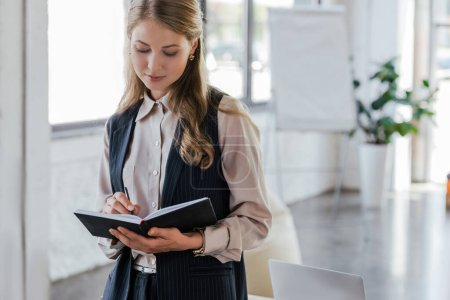 beautiful businesswoman writing in notebook while standing in office